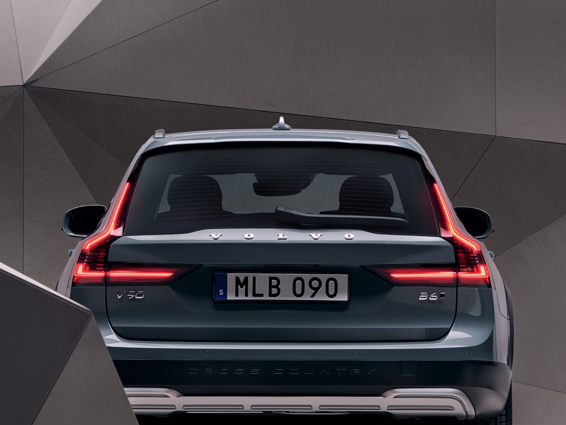 The back exterior of a mussel blue metallic V90 Cross Country standing in front of an artistic wall