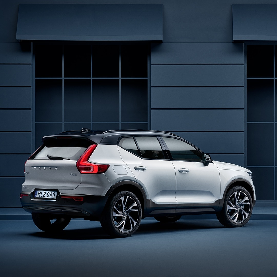 A Volvo XC40 stands parked along a blue facade