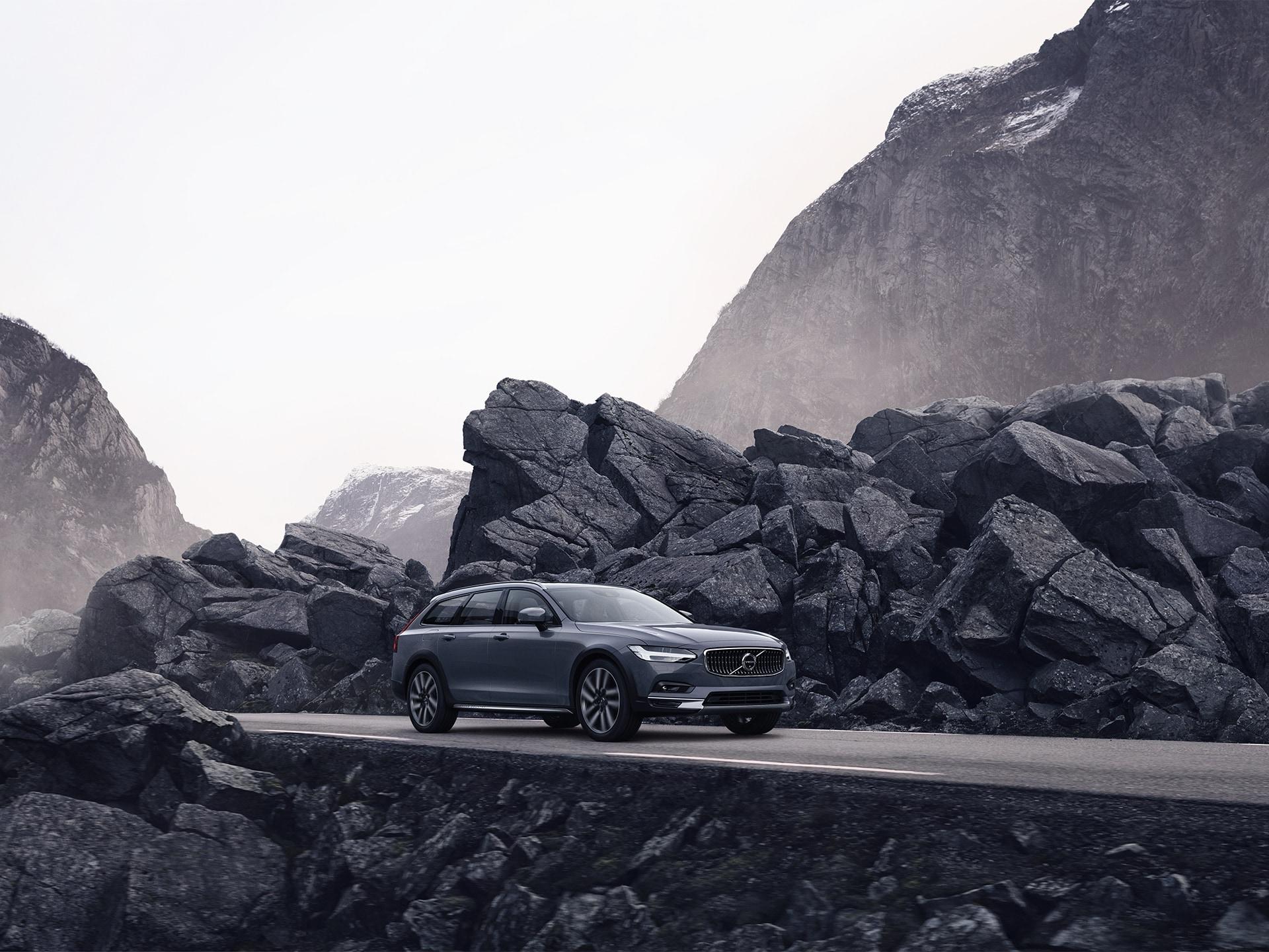 Grár Volvo ekur eftir vegi með stórgrýti til beggja hliða