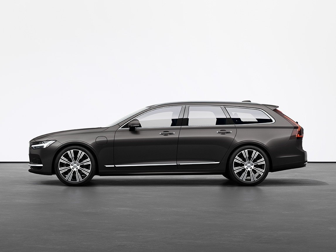 Una station wagon Volvo V90 Recharge Plug-in Hybrid nel colore Pine Grey ferma sul pavimento grigio in uno studio