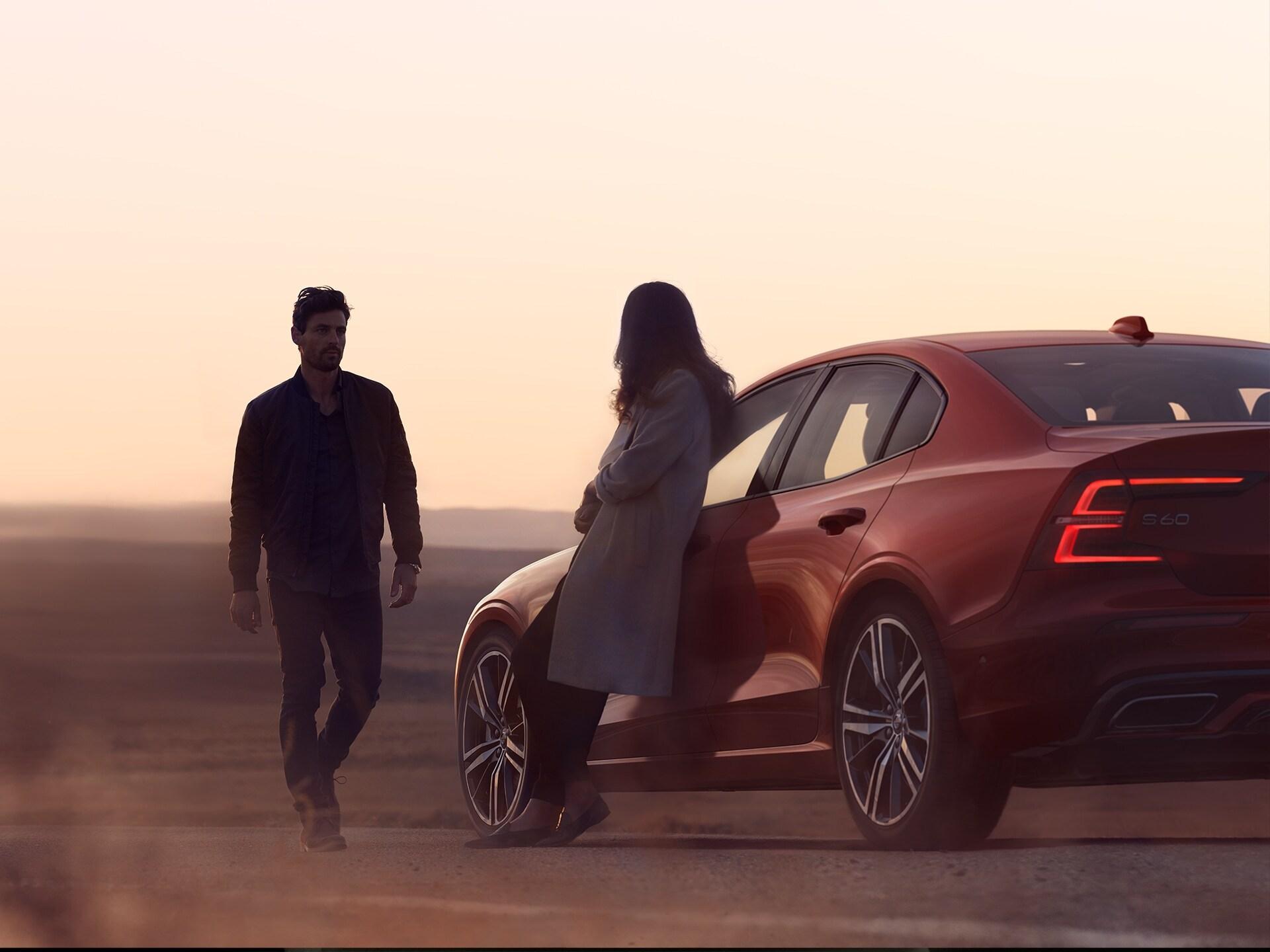 Un uomo e una donna in piedi vicino alla loro S60 rossa, al tramonto.