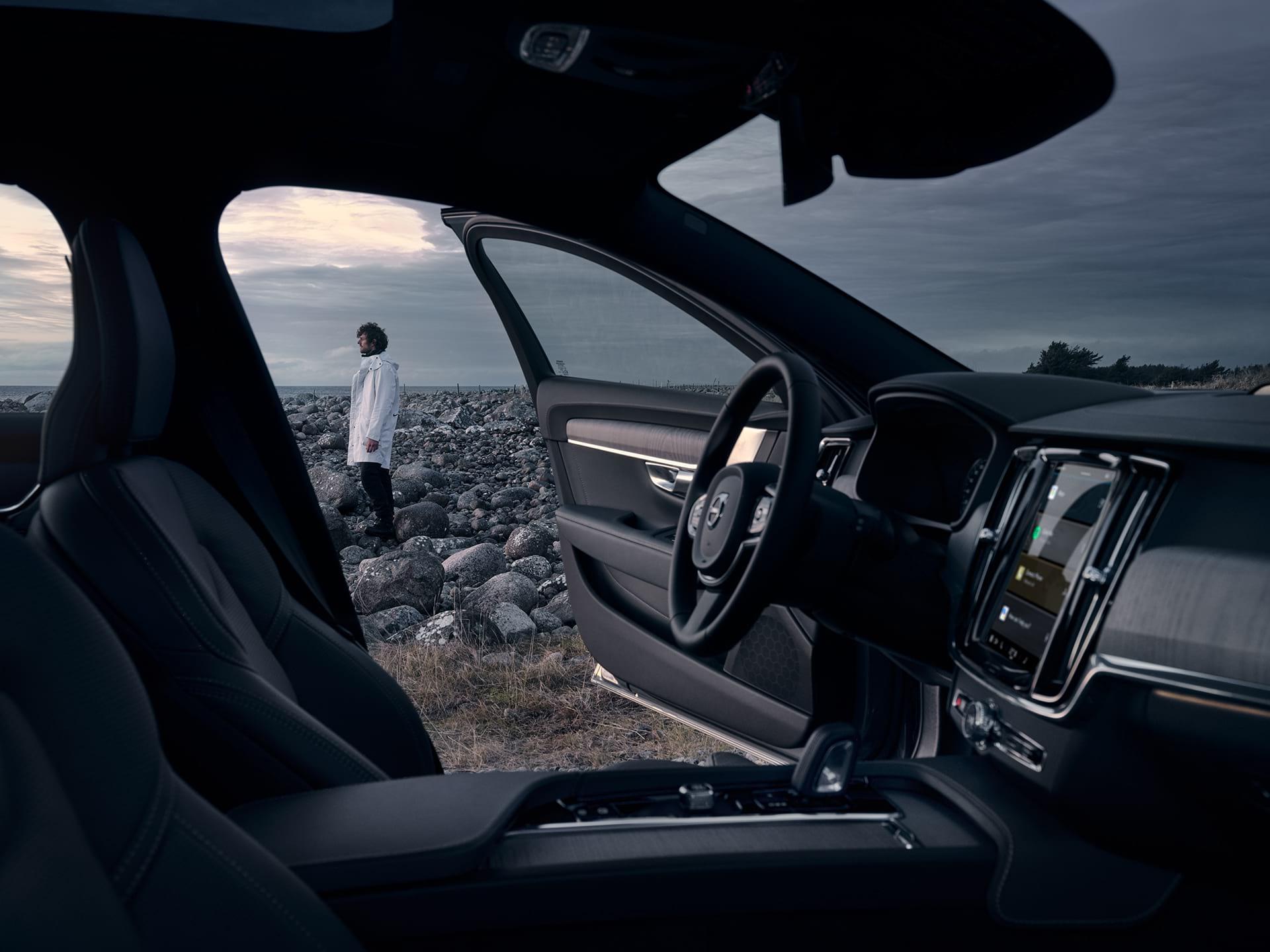 Interno di una V90 Cross Country con interni neri, con un uomo all'esterno.