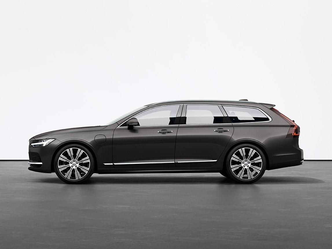 Una Volvo V90 Recharge plug-in hybrid station wagon colore Pine Grey ferma su un pavimento grigio in uno studio