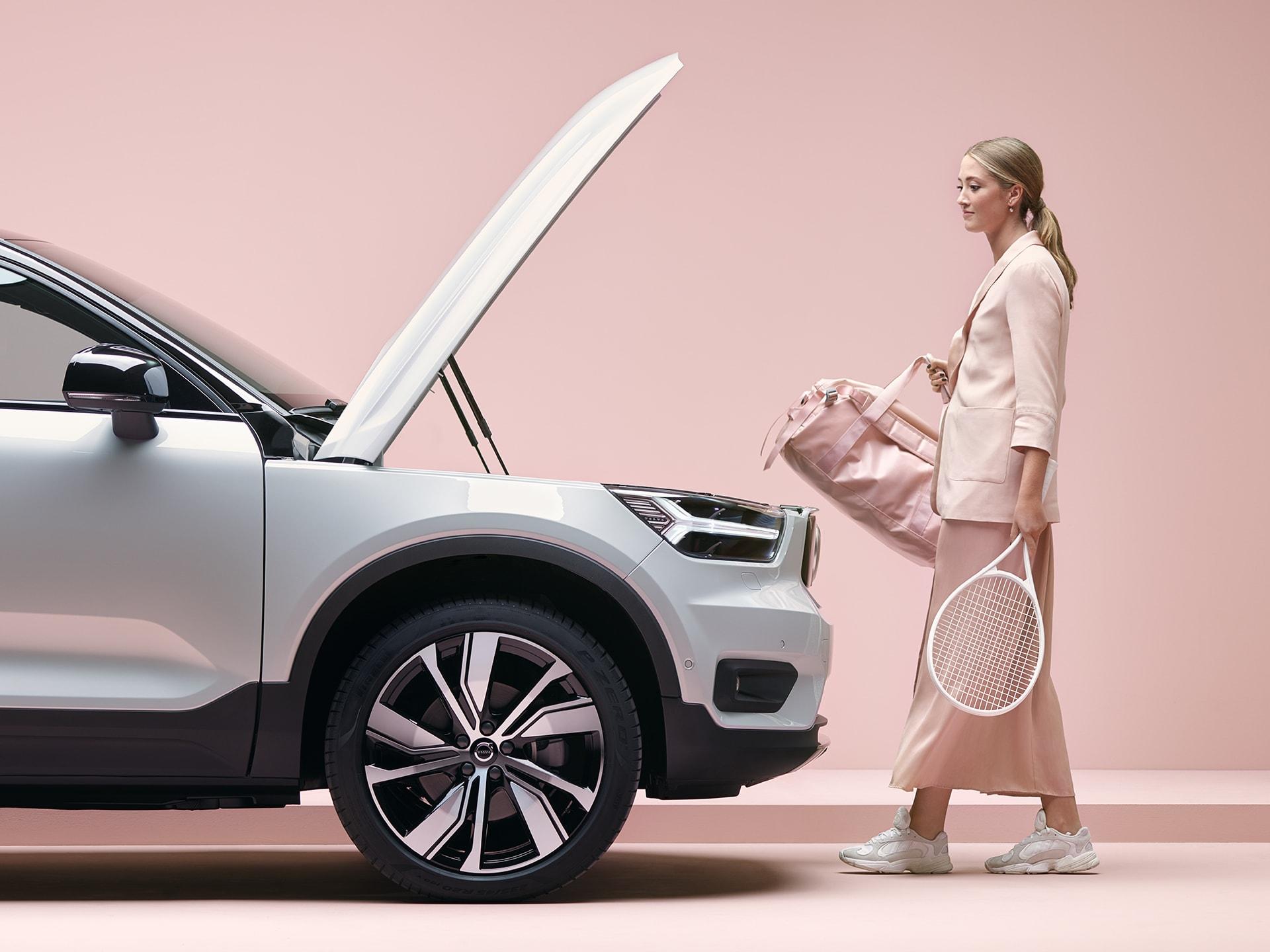 Una ragazza bionda con una sacca sportiva e una racchetta da tennis in mano si dirige verso la sua XC40 Recharge