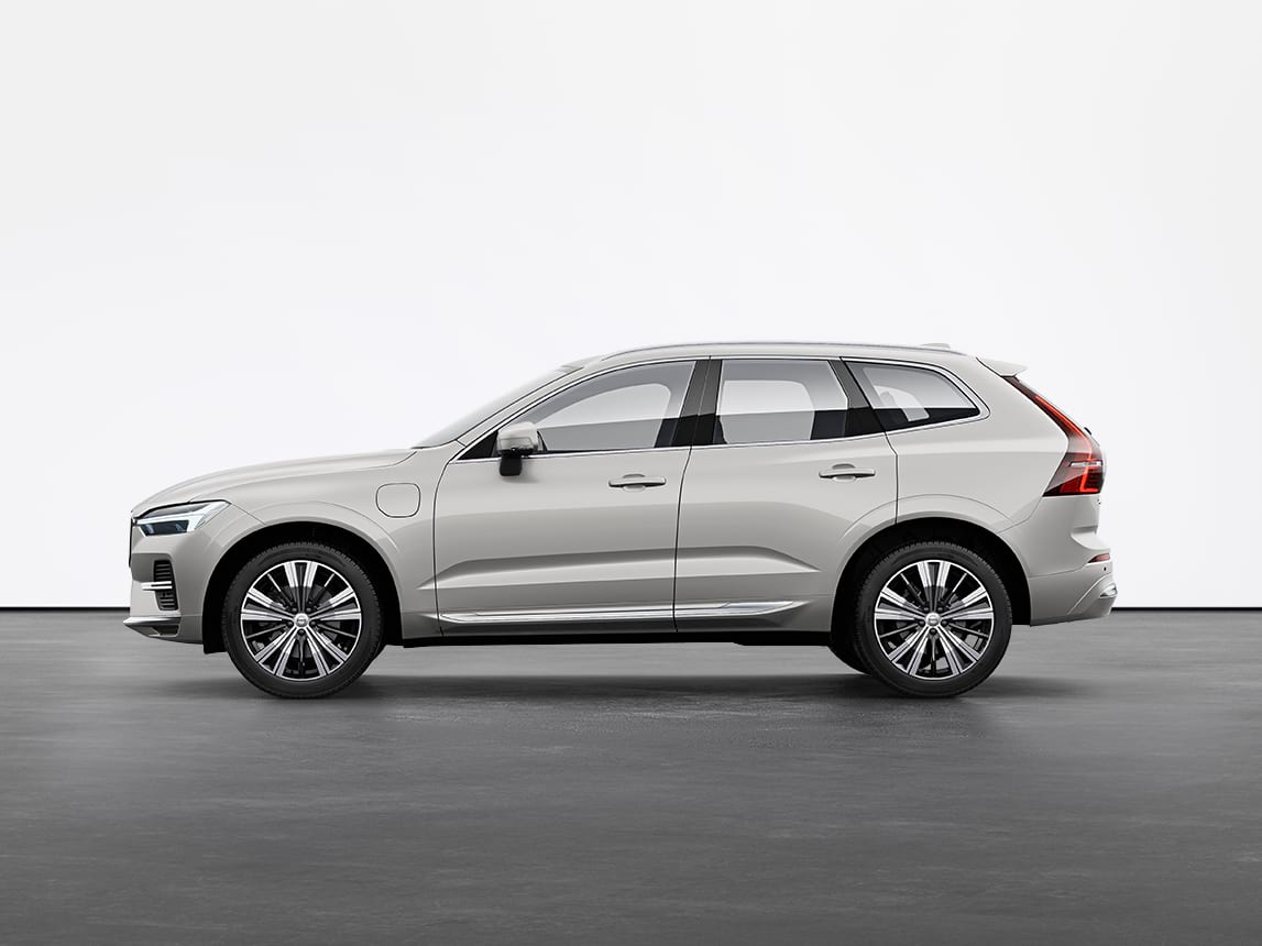 A silver Volvo XC60 Recharge SUV standing still on grey floor in a studio.