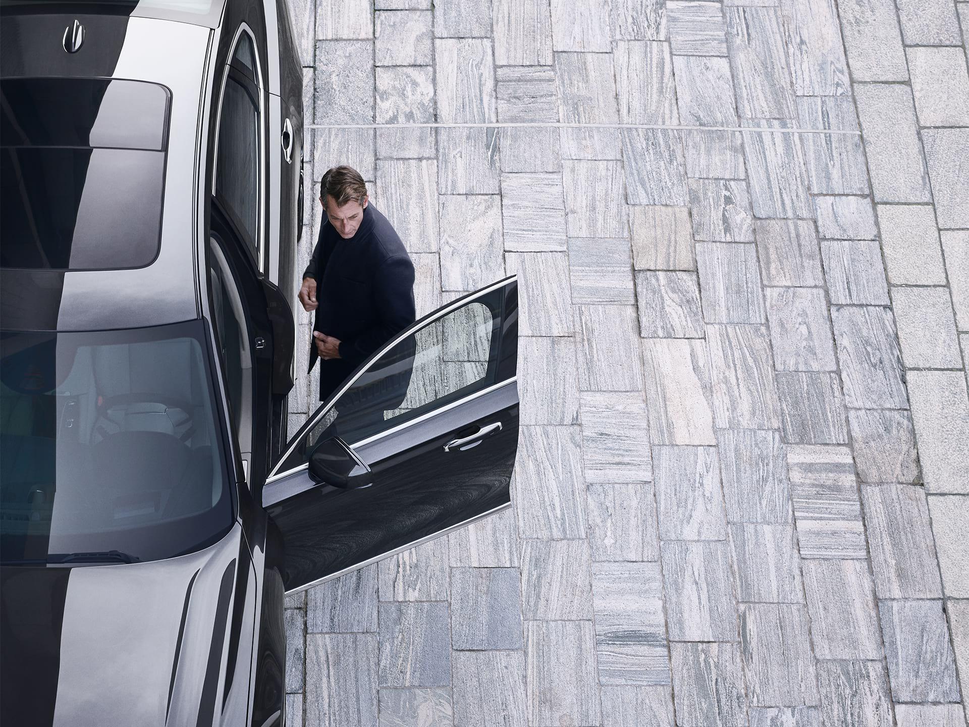Un uomo sta per salire sulla sua Volvo S90.