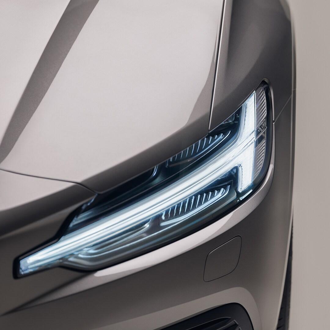 Primo piano dei fari anteriori di una Volvo V60 Recharge beige.