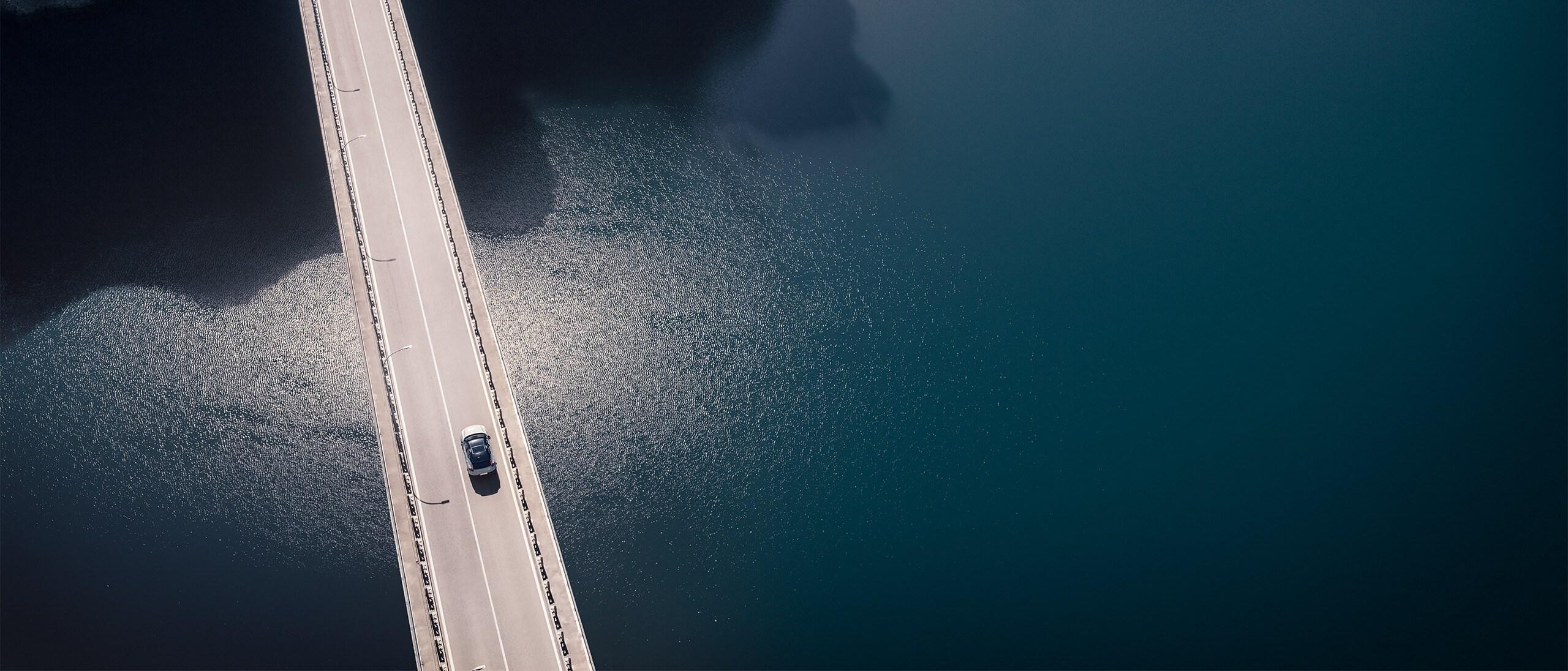 Vista aerea di un nuovo SUV XC40 Recharge Pure Electric mentre attraversa un ponte a due corsie su uno specchio d'acqua calmo grigio scuro, diretto verso una galleria.