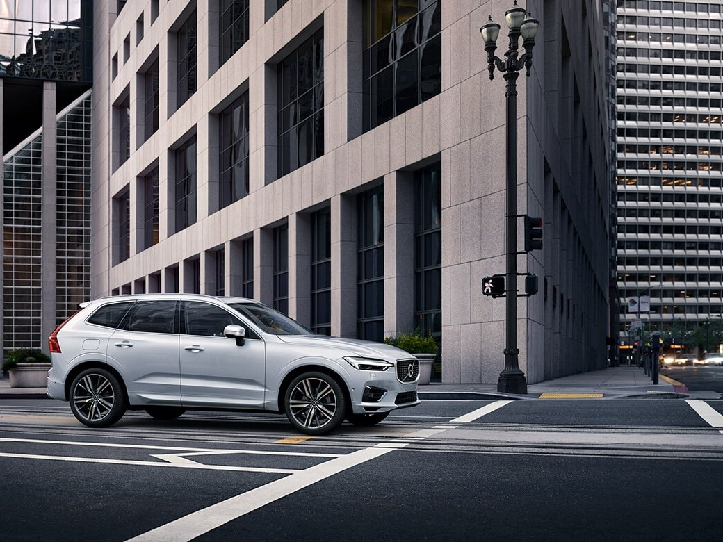 Side view of a silver Volvo XC60 waiting at a stop light in a downtown urban environment.