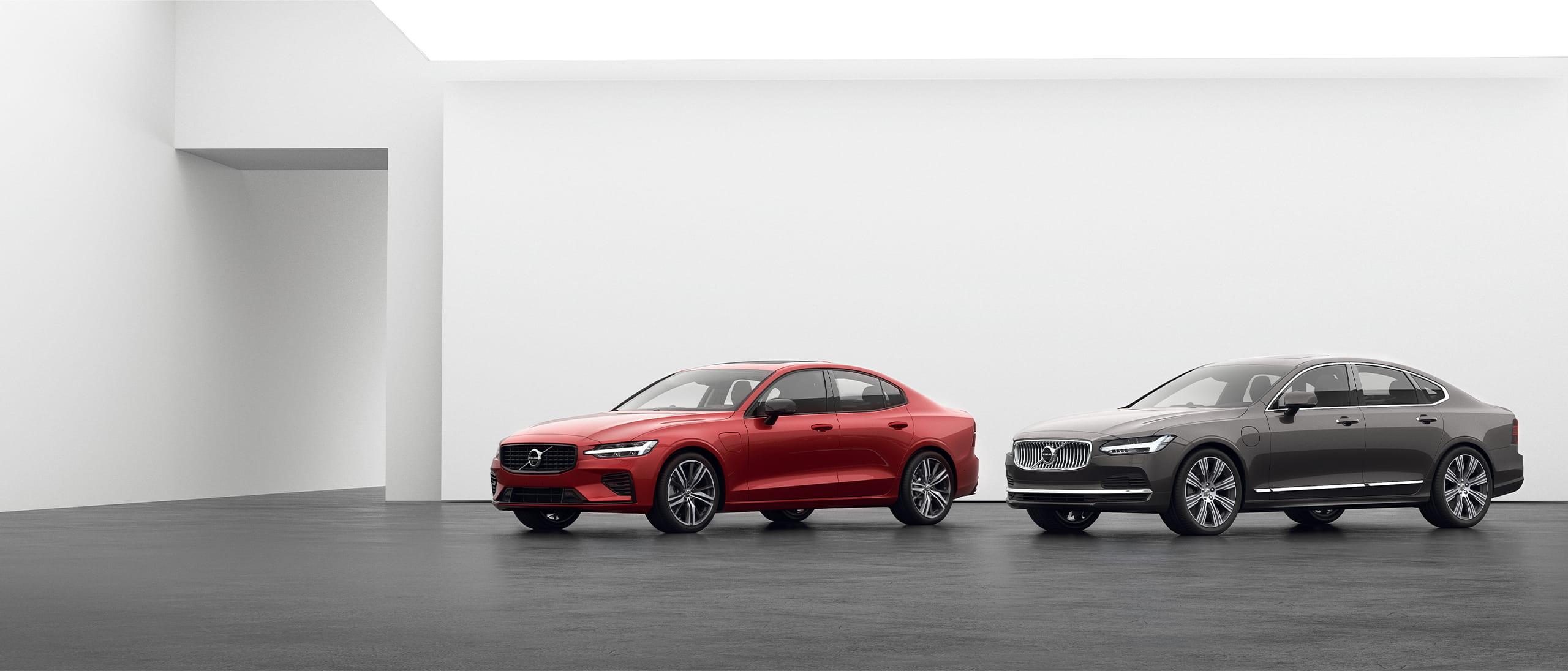 회색 바닥에 주차된 Volvo S90 및 Volvo S60 Recharge 플러그인 하이브리드