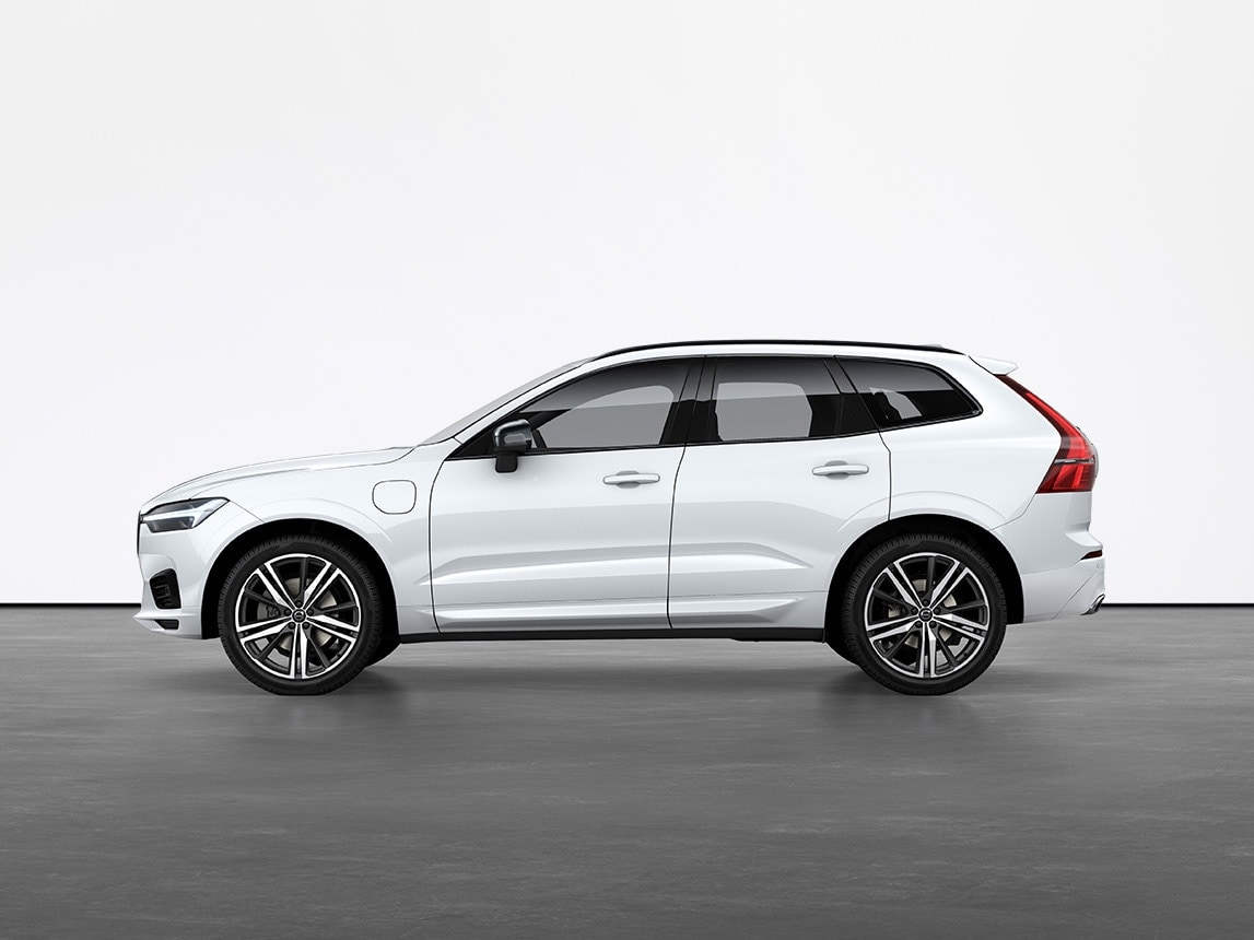 A crystal white Volvo XC60 Recharge plugin hybrid SUV standing still on grey floor in a studio