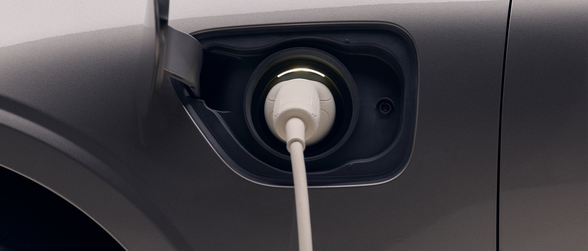 Closeup of the front left quarter of a new dark grey Volvo electric car, with a white charging cable plugged in to the car's charging port.