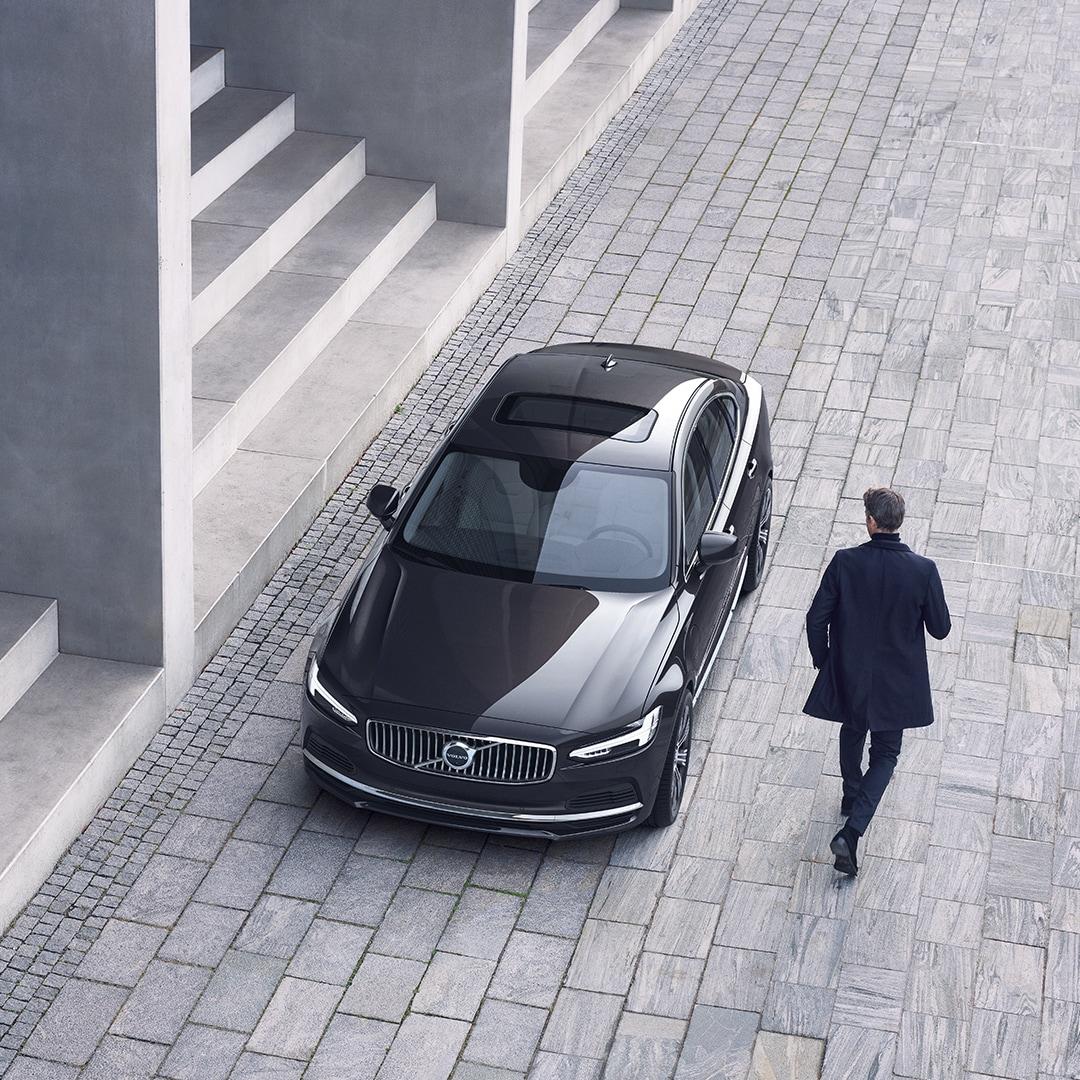 """""""Volvo S90"""" pastatytas priešais laiptus, vyras eina link automobilio."""