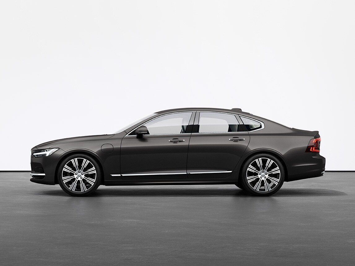 Berline Volvo S90 Recharge Plug-in hybride Platinum Grey Metallic, sur un sol gris dans un studio