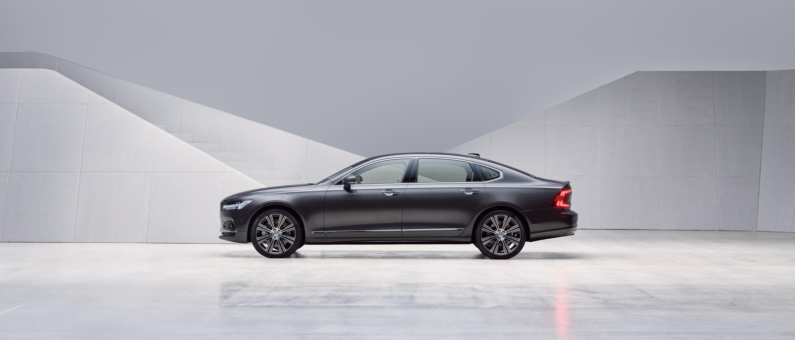 Tamni Volvo S90 parkiran ispred sivog zida.