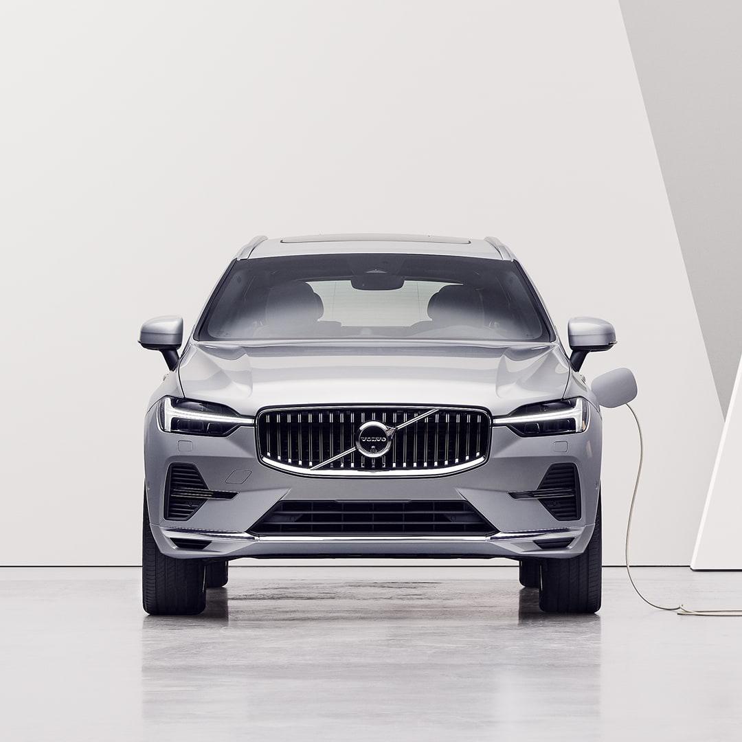 Жена гледа во Volvo XC60 Recharge приклучен во столб за полнење и се полни.