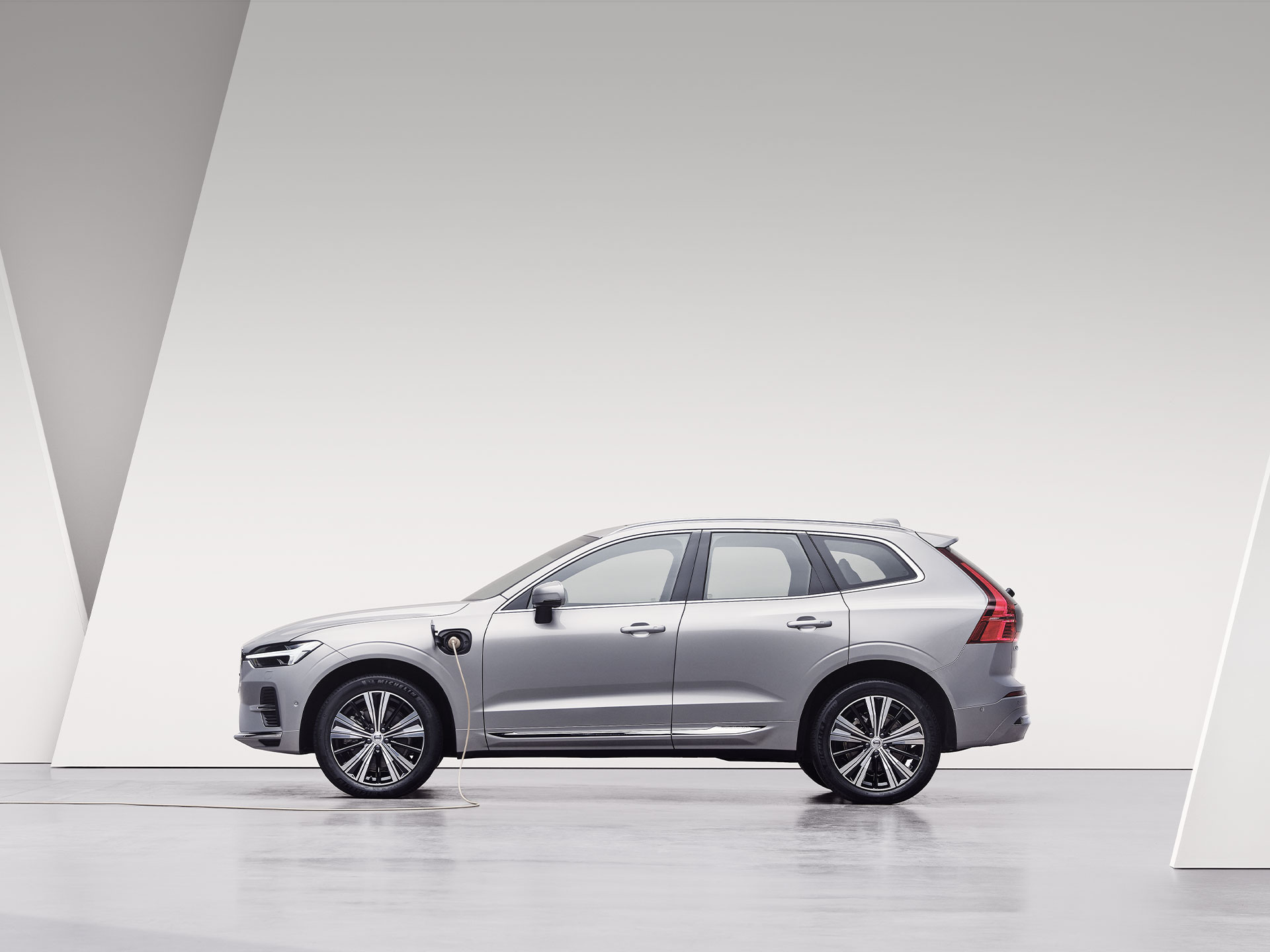 A silver Volvo XC60 Recharge, charging in white surroundings.
