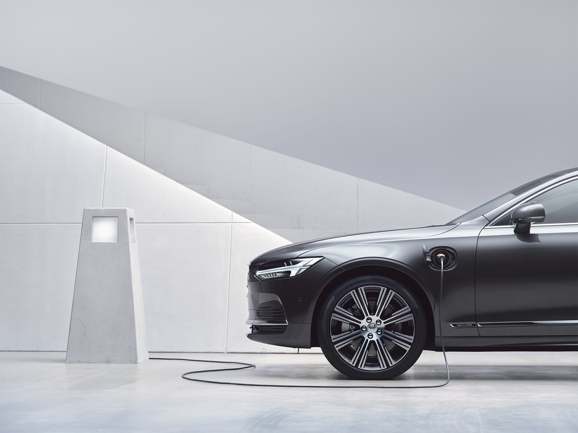 A Volvo S90 Recharge gets charged at a charging station.