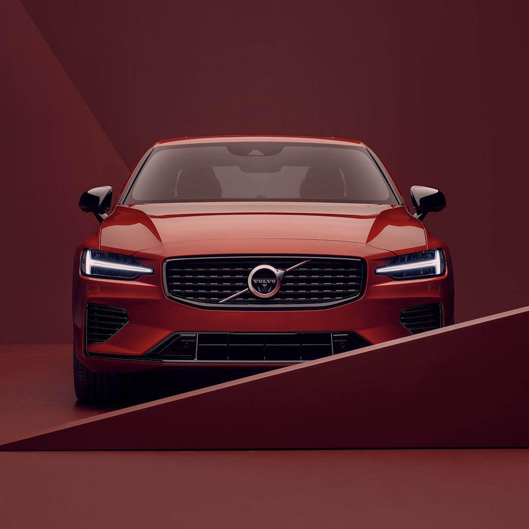 The front exterior of a red Volvo S60 Recharge in red surroundings.
