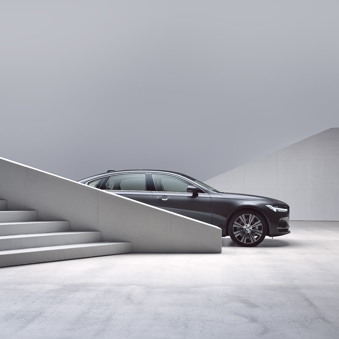 A Volvo S90 partially obscured by stairs.
