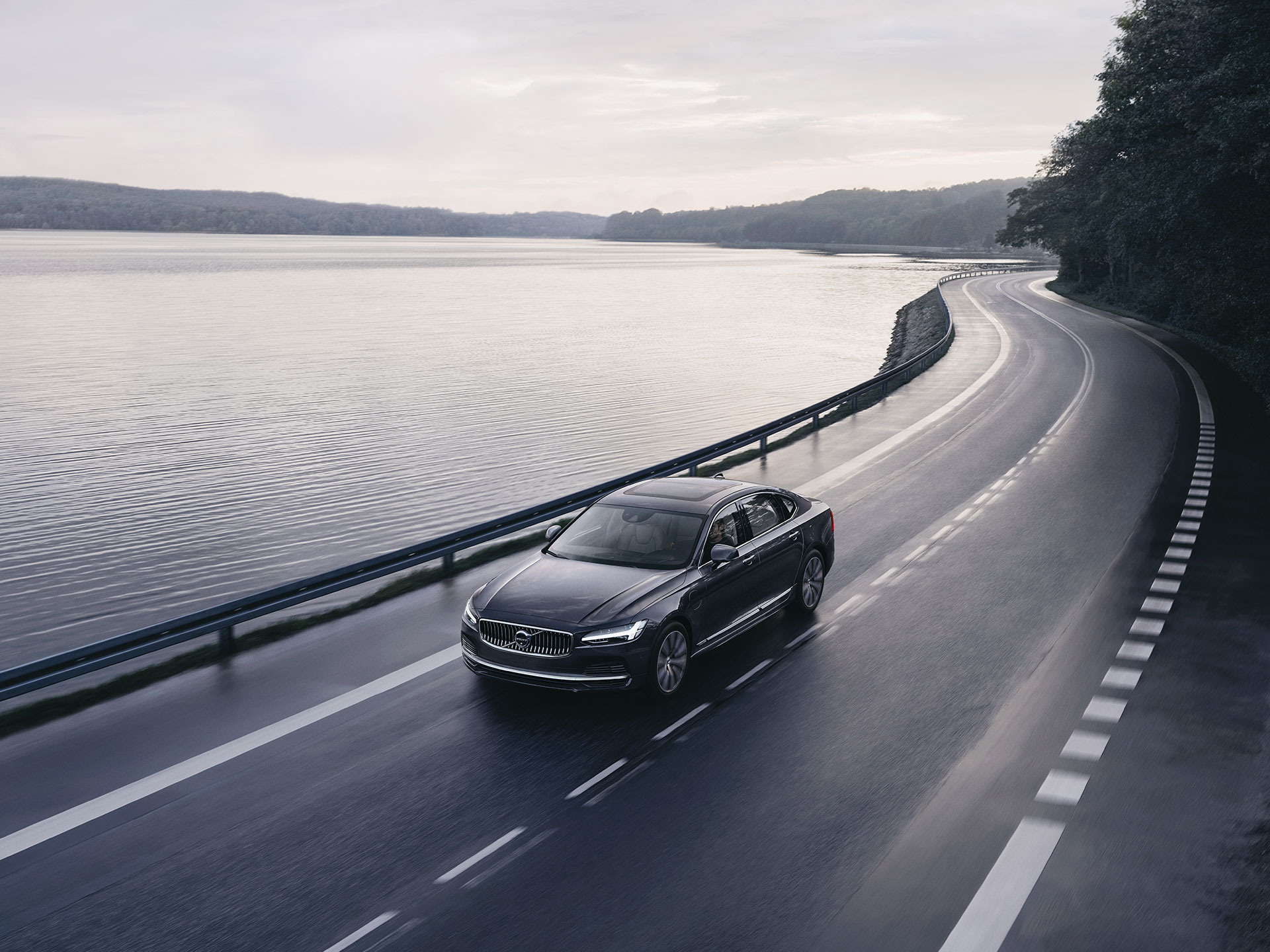 A Volvo S90 mild hybrid driving on a coastal road.