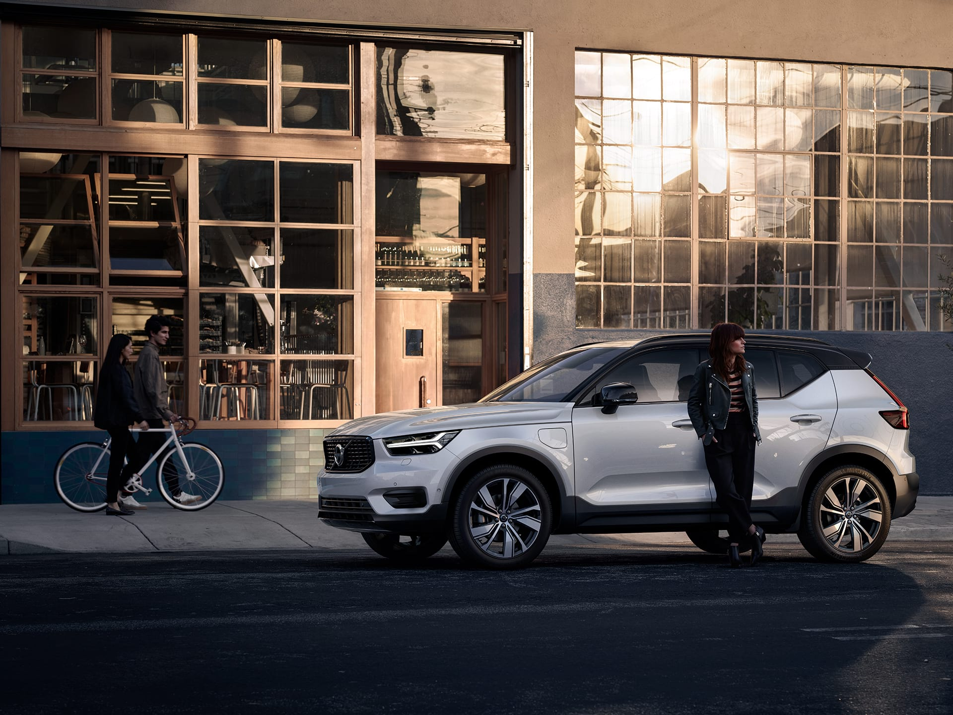 A woman stands leaning against a white XC40 Recharge plug in hybrid, behind her is a restaurant.