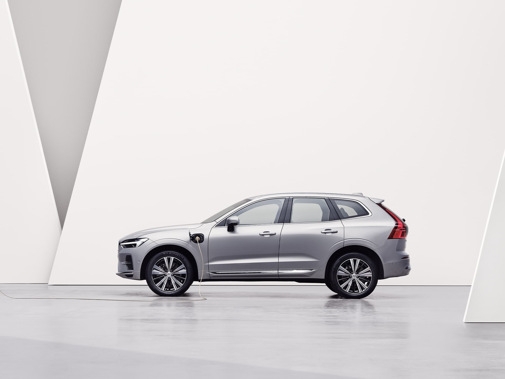 A silver Volvo XC60 Recharge, charging in a white surrounding.