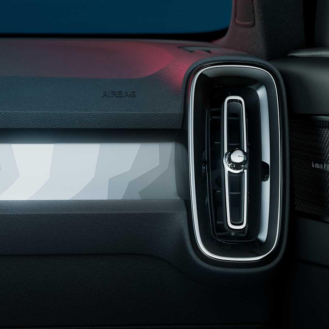 Un Volvo C40 recharge azul fiordo estacionado en un cuarto azul oscuro.