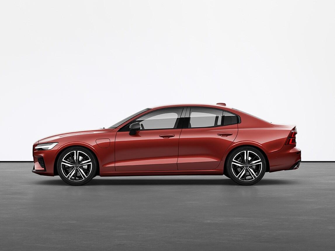 Un Volvo Sedán S60 Recharge híbrido recargable de color rojo sobre un suelo gris en el estudio
