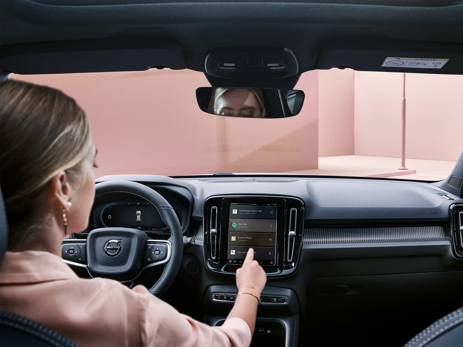 Una mujer dentro de un auto Volvo XC40 Recharge, usando el sistema de conectividad