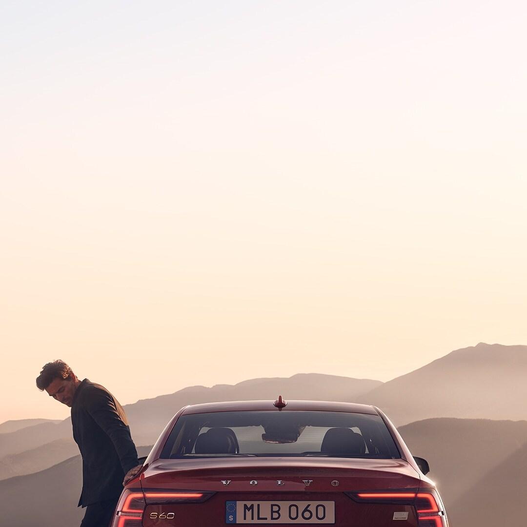 Un hombre inclinado sobre su Volvo S60 Recharge rojo