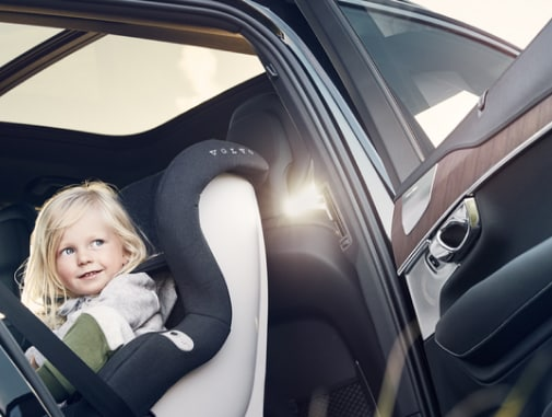 A rearward-facing child car seat with a young girl sitting in the back seat of a Volvo car.