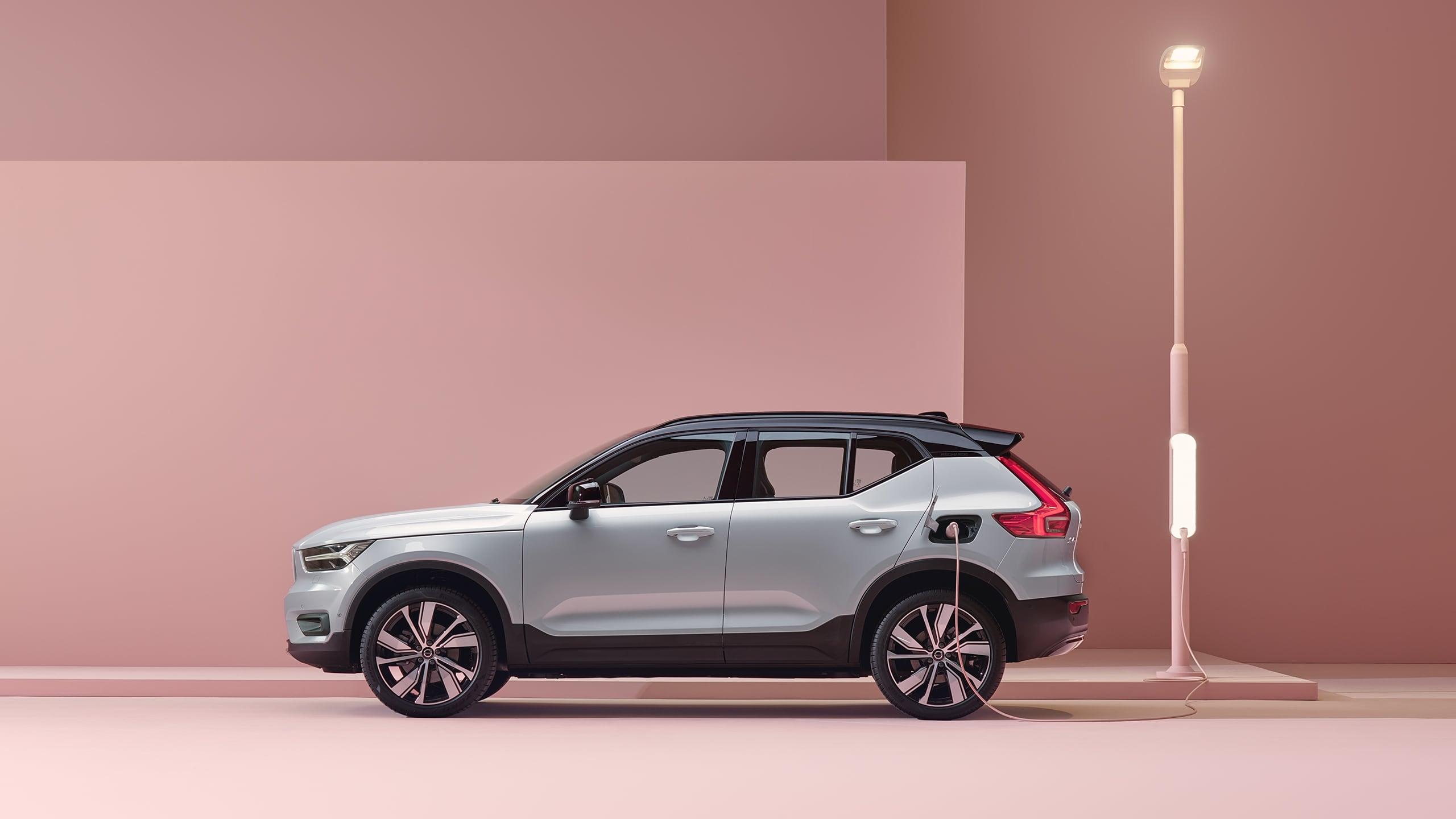 Een grijze 100% elektrische Volvo XC40 SUV wordt opgeladen in een roze stadsomgeving