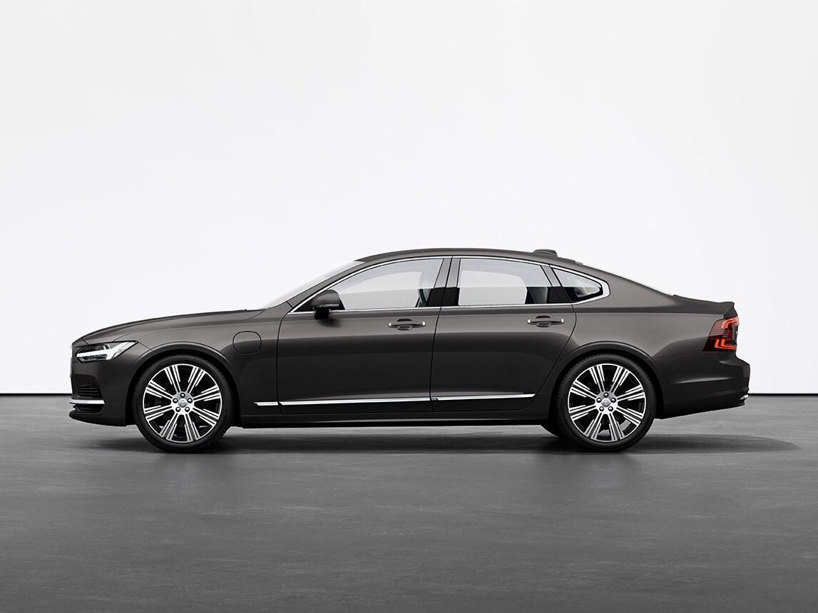 A platinum grey Volvo Sedan S90 Recharge plugin hybrid standing on grey floor in studio