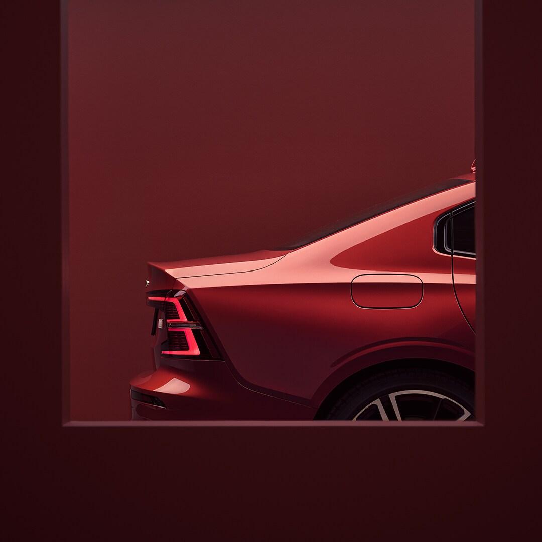 De achterkant van een rode Volvo S60 in een rode omgeving.