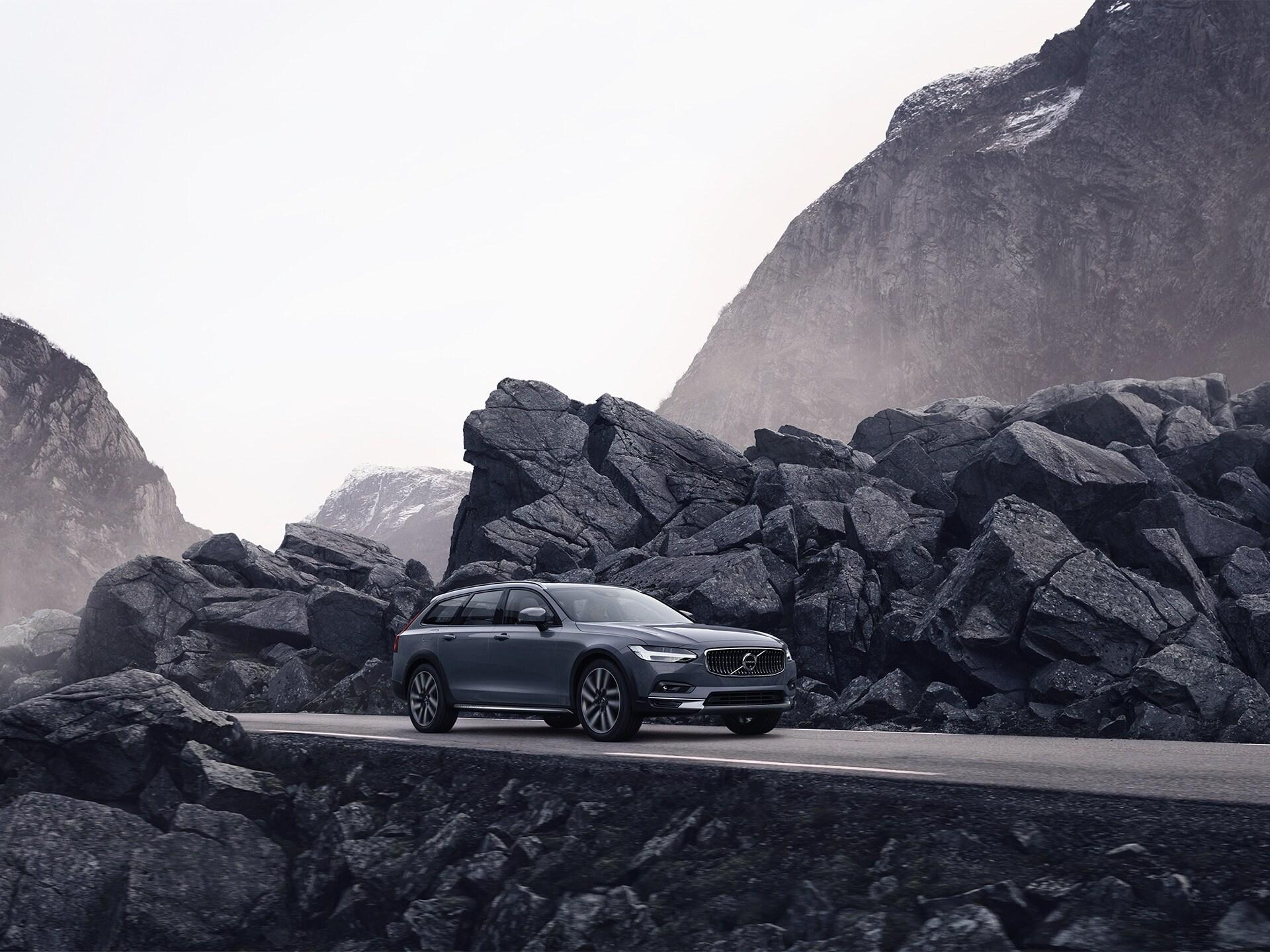 Een grijze Volvo rijdt op een weg met rotswanden.