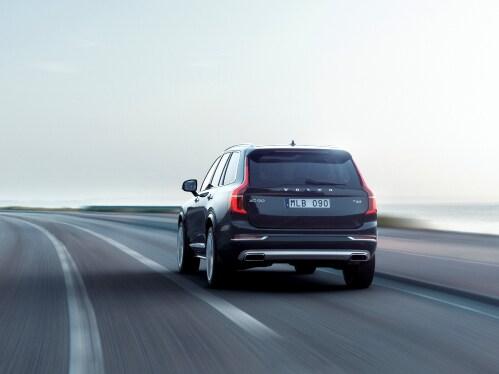 Een rijdende, zwarte Volvo XC90 van achteren gezien.