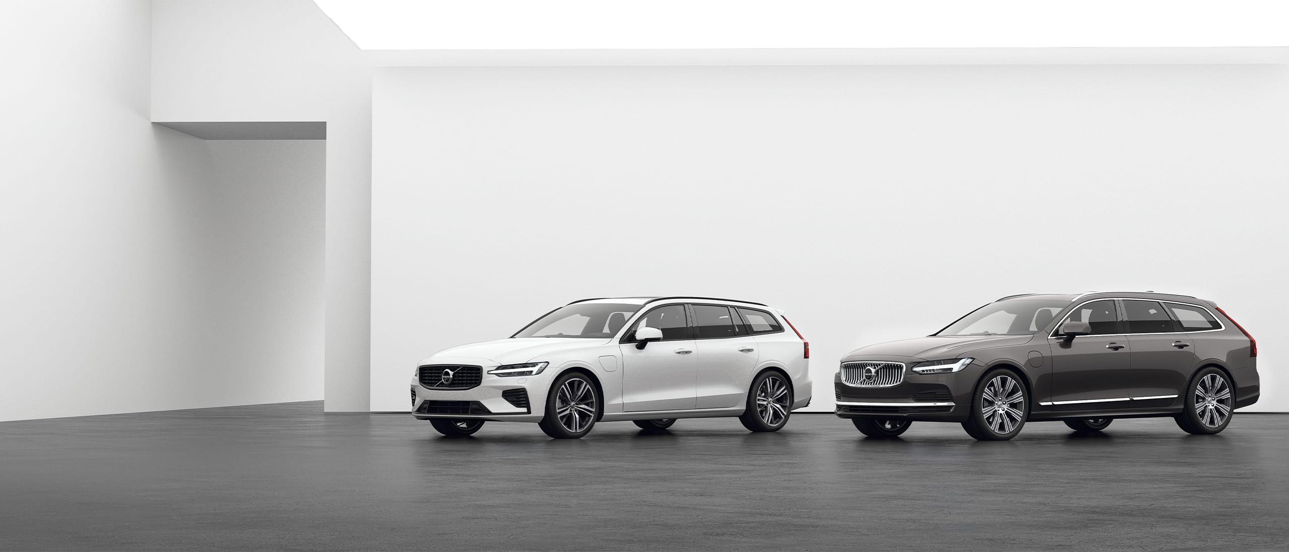 Een Volvo Estate V90 en een Volvo Estate V60 Recharge staan op een grijze vloer