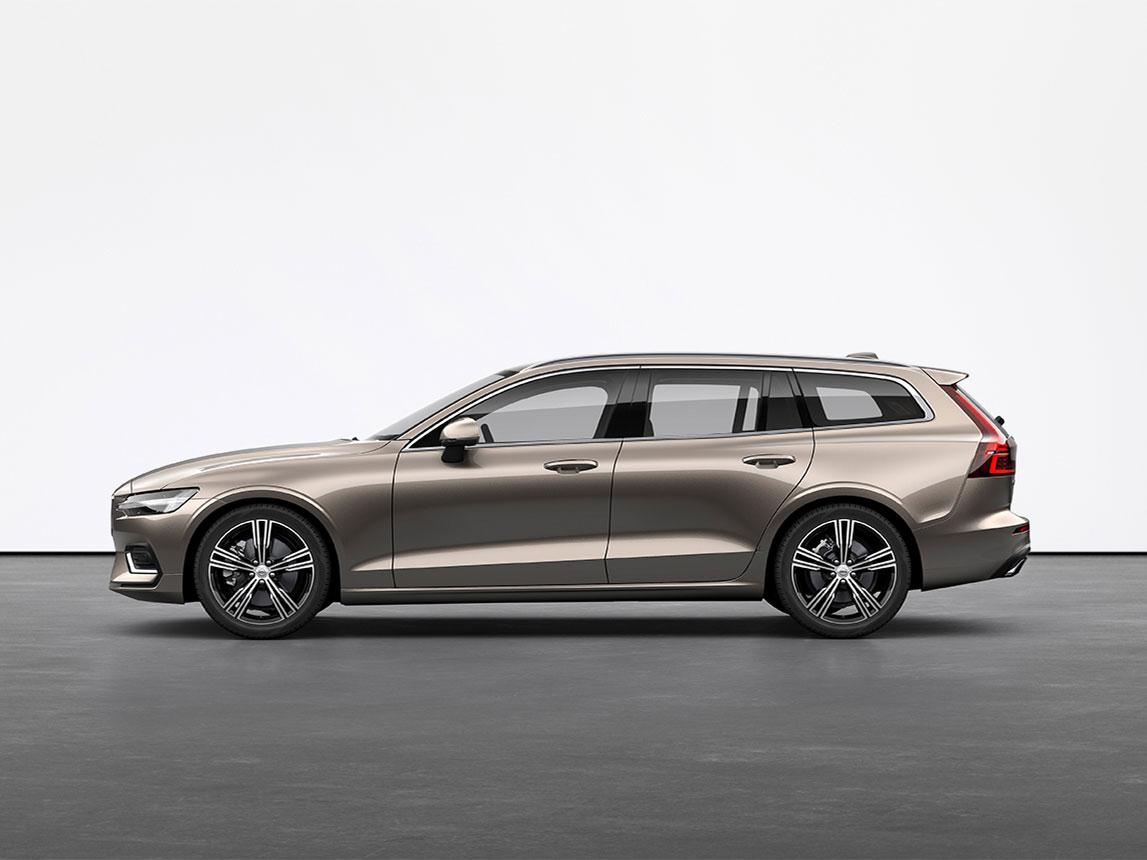 Een licht zandkleurige metallic Volvo estate V60 die stilstaat op de grijze vloer van een studio