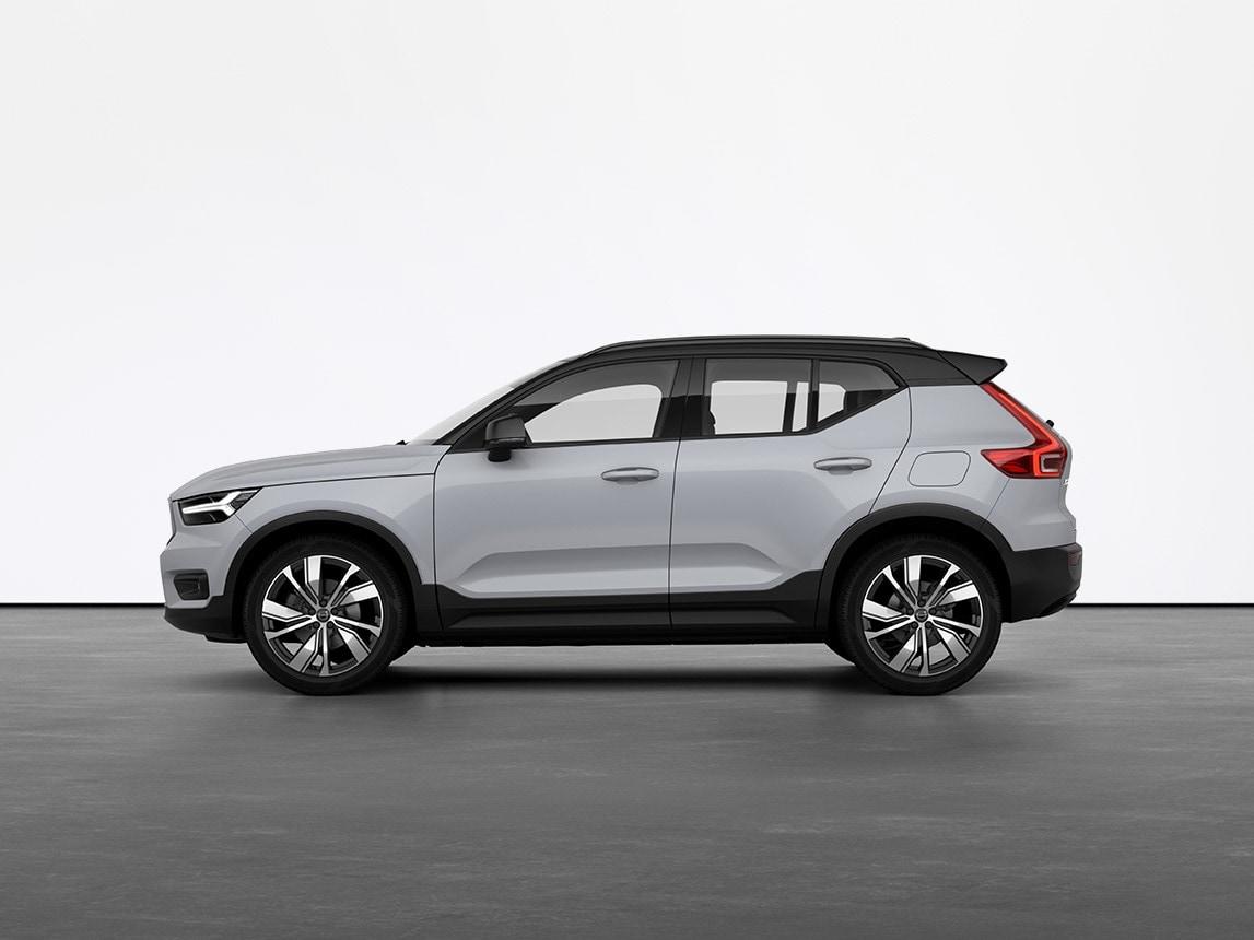 Een grijze volledig elektrische, compacte Volvo XC40 SUV die stilstaat op de grijze vloer van een studio