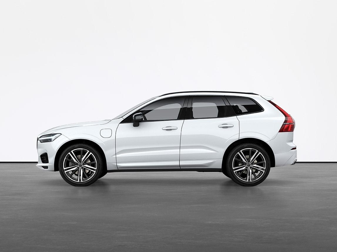 Een kristalwitte Volvo XC60 Recharge Plug-in hybrid SUV die stilstaat op de grijze vloer van een studio