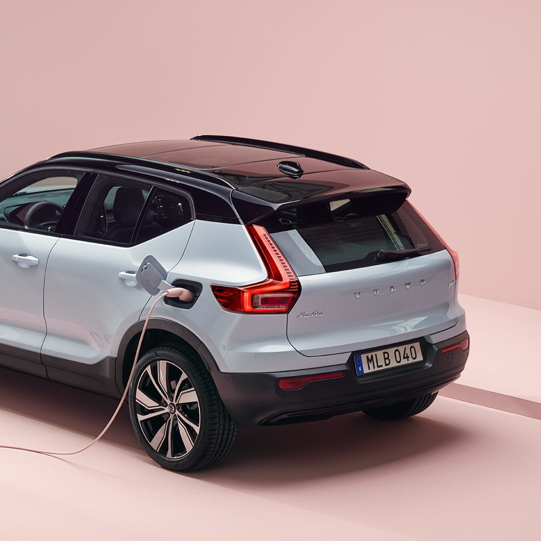 A grey Volvo XC40 Recharge, charging in a pink surrounding