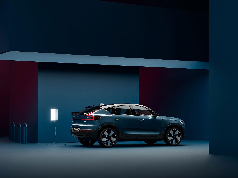 Een Volvo C40 Recharge staat geparkeerd in een donkerblauw vertrek naast een laadpaal.