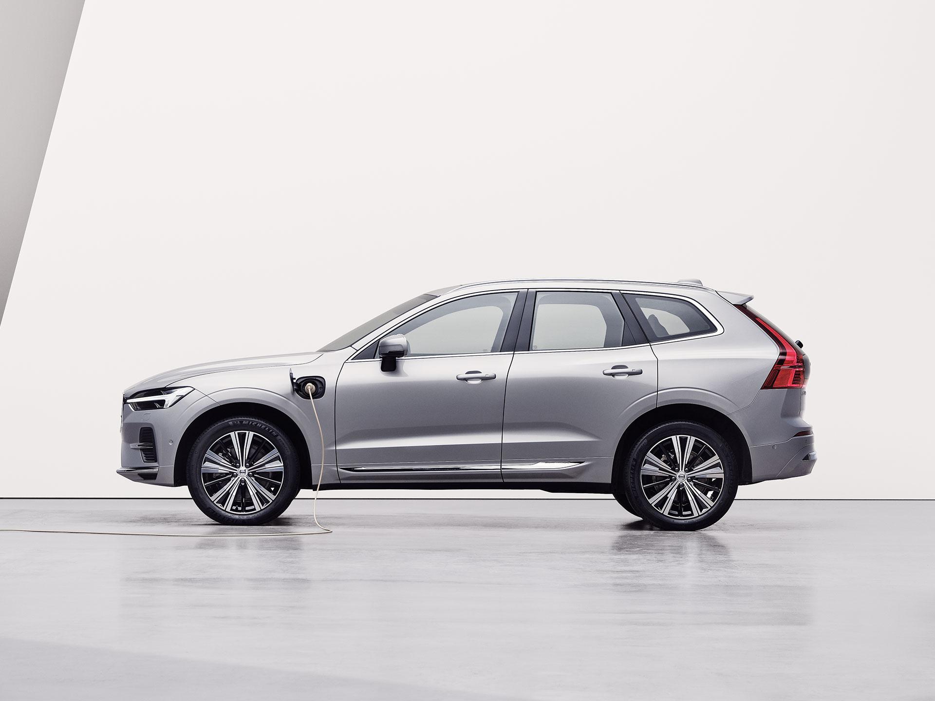 Een zilverkleurige Volvo XC60 Recharge, die wordt opgeladen in een witte omgeving