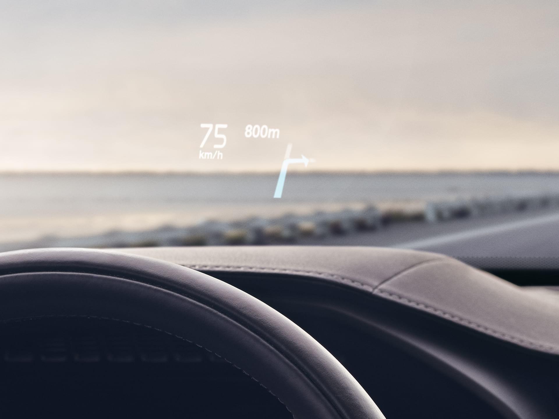 Binnenin een Volvo, waarbij de head-updisplay de rijsnelheid en navigatie op de voorruit weergeeft.