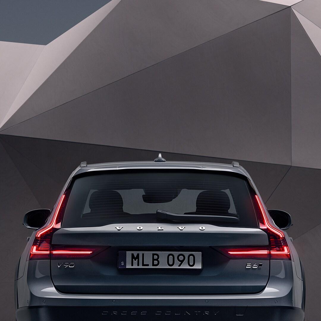 De achterkant van een mosselblauwe metallic Volvo V90 Cross Country die voor een artistieke wand staat.