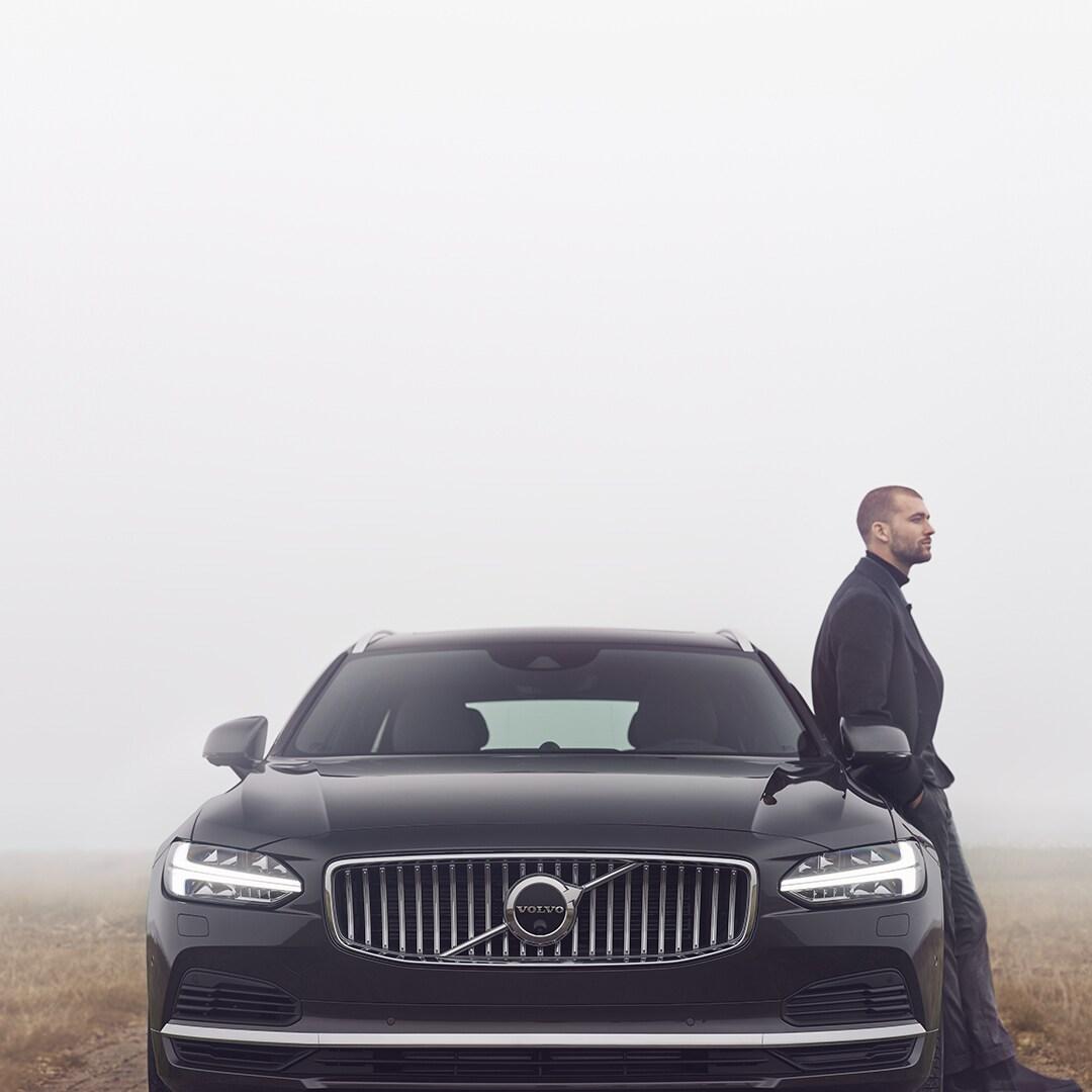 Een man leunt tegen zijn Volvo V90. Buiten is het bewolkt.