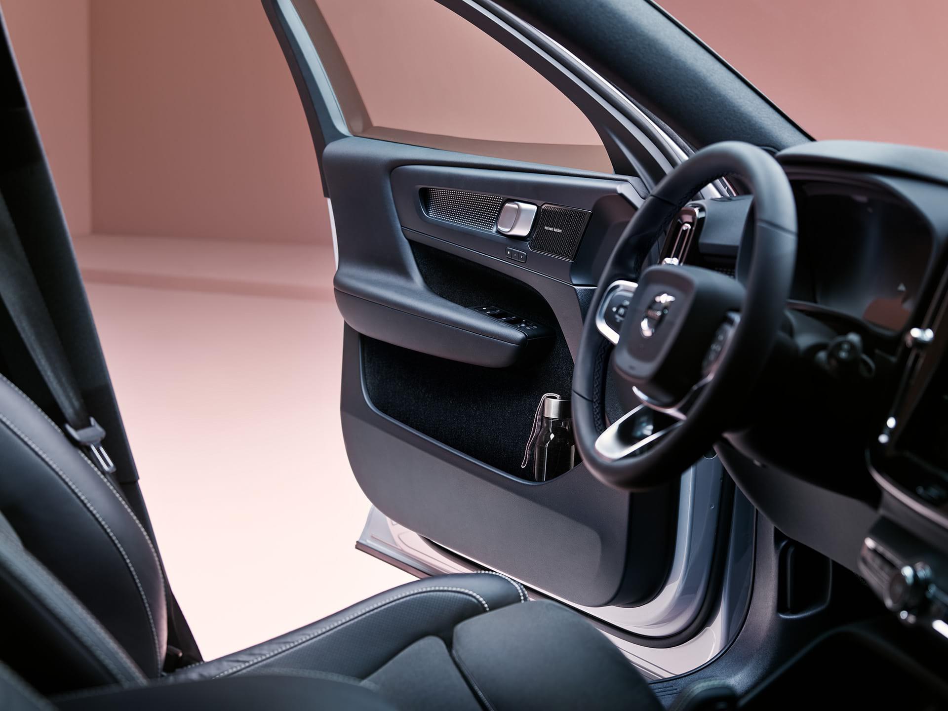 De binnenkant van een Volvo XC40 Recharge met zwart interieur, het bestuurdersportier staat open met daarin een waterfles.