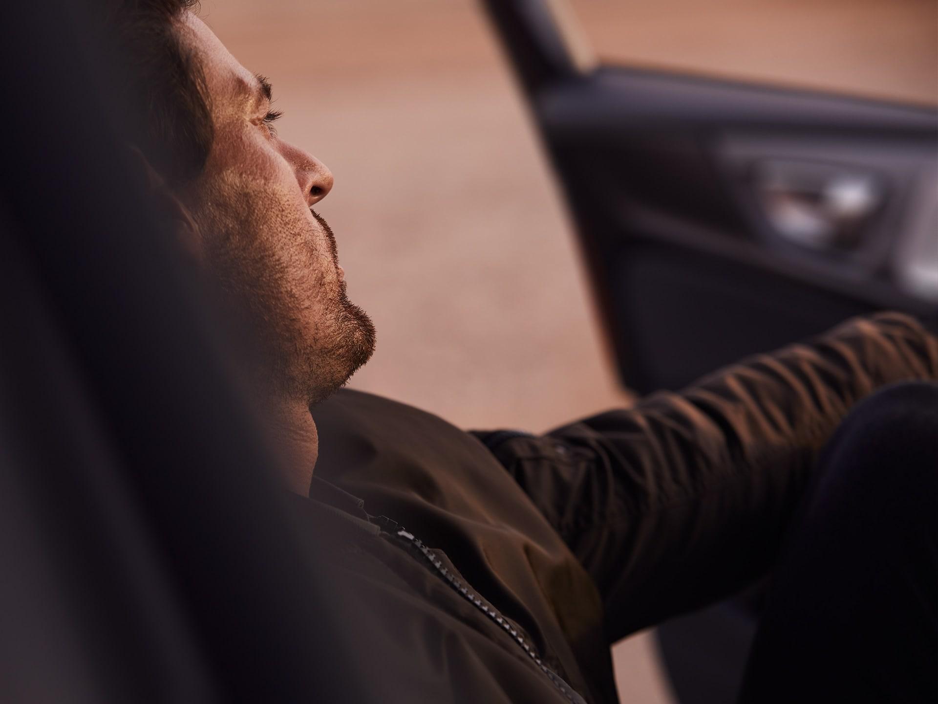 Een man zit met de deur open in zijn auto en kijkt naar buiten