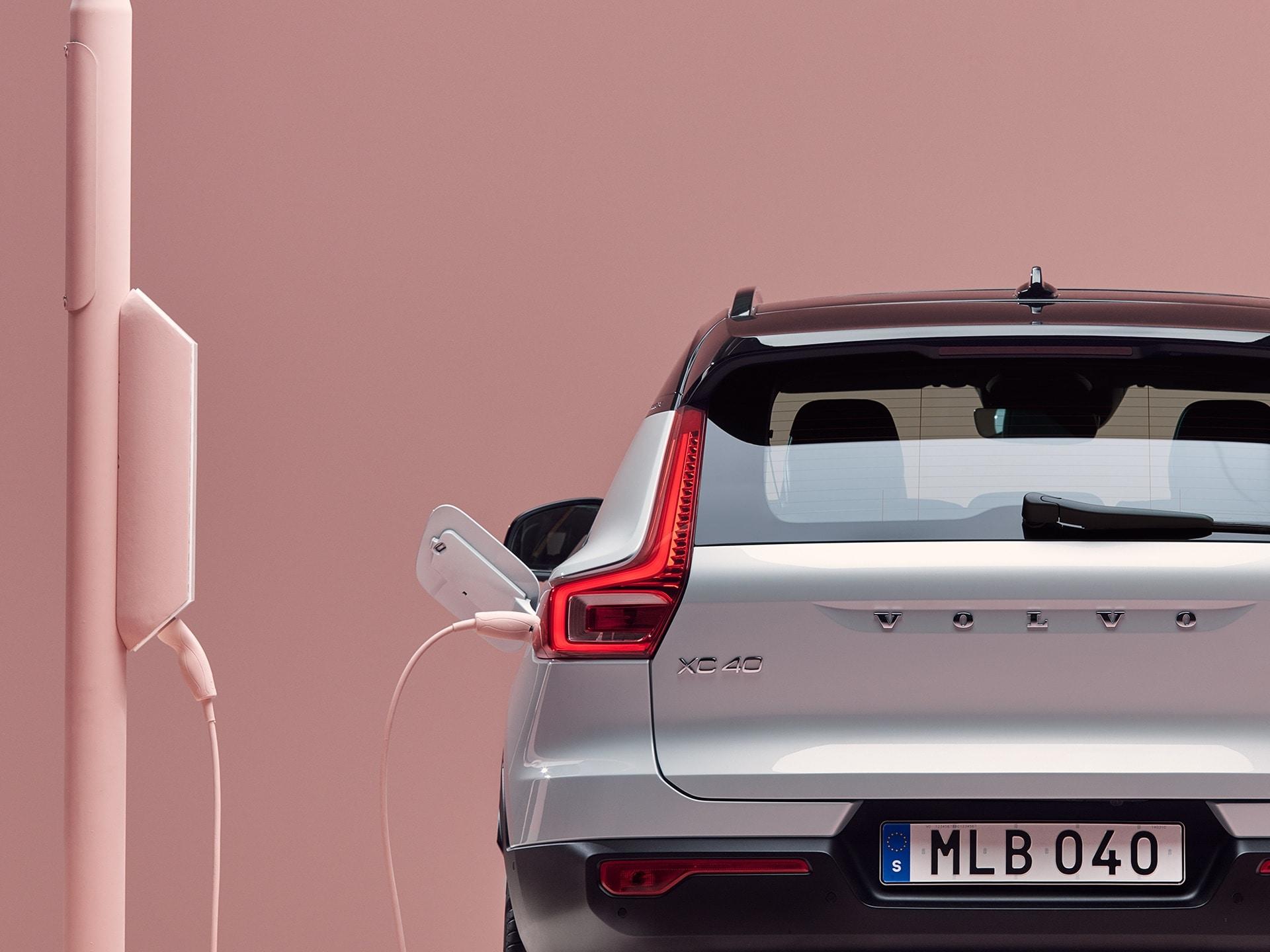 Beeld van de achterkant van een Volvo XC40 Recharge Pure Electric SUV die is aangesloten op een laadpunt aan een lantaarnpaal.